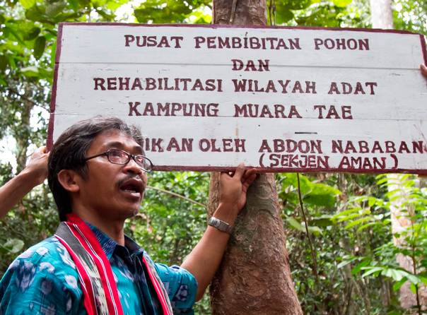 Abdon Nababan, secretary general of the Aliansi Masyarakat Adat Nusantara, a network of indigenous groups, stands near a sign in a forest in Indonesia. Photo: Sigit Pratama
