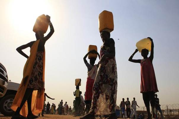 Displaced people carry water containers on their heads at Tomping camp near South Sudan's capital Juba January 7, 2014. REUTERS/James Akena