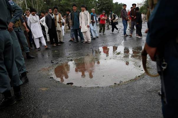 People look at a crater caused by a bomb blast in Kabul June 6, 2014. REUTERS/Ahmad Masood