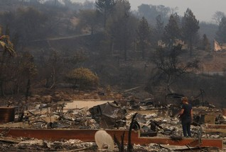 A woman surveys the remains of a home destroyed by wildfire in Napa