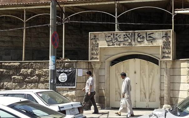 People walk past a banner (in black and white) belonging to the Islamic State in Iraq and the Levant (ISIL) in the city of Mosul, June 28, 2014 REUTERS/Stringer
