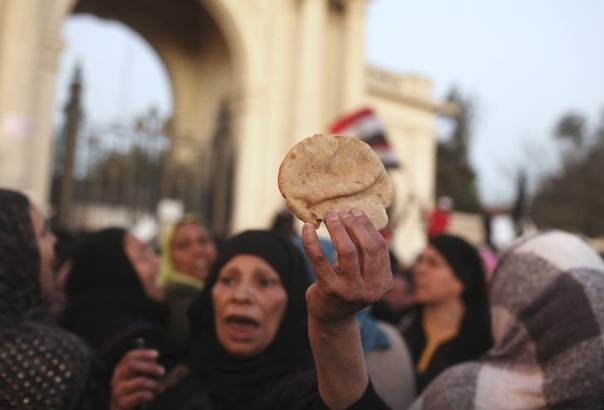 An anti-Mursi protester holds up bread to symbolise the lack of food and high food prices while chanting anti-Mursi slogans during a protest in front of the gate of El-Quba, one of the presidential palaces, in Cairo February 15, 2013. REUTERS/Asmaa Waguih