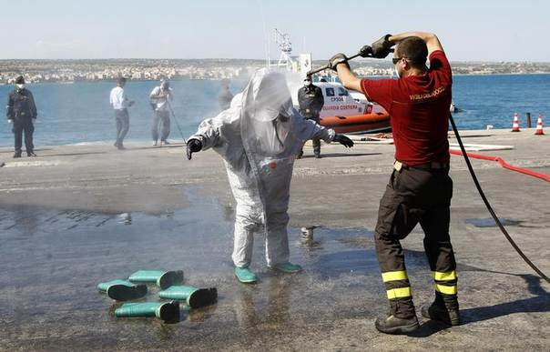 A firefighter cleans his colleague after he disembarked from a boat, on which some 30 bodies were found, after the Italian Navy towed it into the Sicilian harbour of Pozzallo, Italy, July 1, 2014. REUTERS/Antonio Parrinello