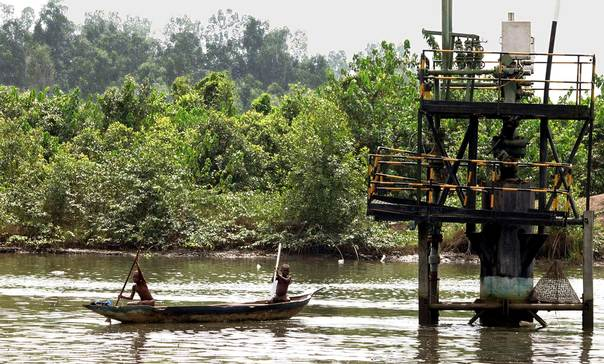 In a 2006 file photo, children paddle a canoe near an oil well head in Odidi near Okerenkoko in the creeks of the volatile oil rich Niger delta in Nigeria. REUTERS/George Esiri
