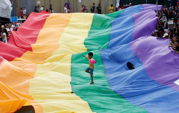 In a 2012 file photo, a boy plays on a rainbow flag during a gay pride march in Manila. REUTERS/Cheryl Ravelo