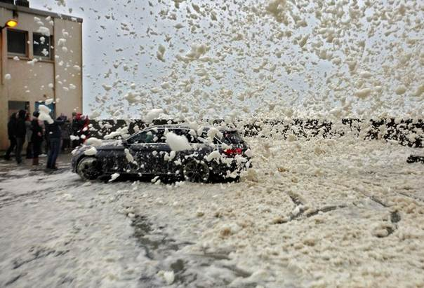 A car turns away from blowing sea foam on the Brittany coast
