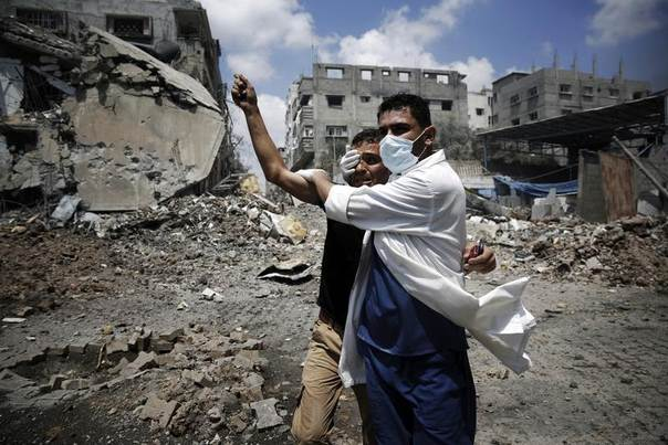 A medic helps a Palestinian in the Shejaia neighbourhood, which was heavily shelled by Israel during fighting, in Gaza City July 20, 2014. REUTERS/Finbarr O'Reilly