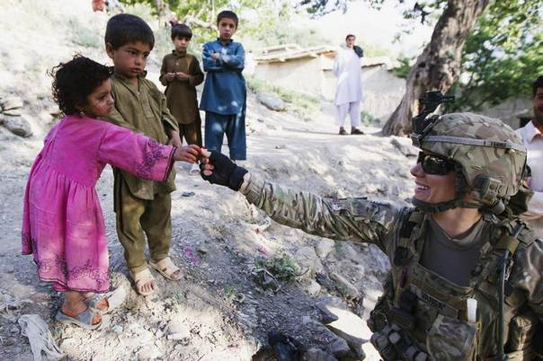 A member of a Female Engagement Team attached to Chosen Company of the 3rd Battalion (Airborne), 509th Infantry gives candy to children, while on a helicopter assault mission to improve their biological database of fighting aged males, near the town of Ahmad Khel in Afghanistan's Paktiya Province July 16, 2012. REUTERS/Lucas Jackson