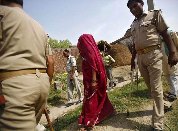 The veiled mother of one of the two teenage girls, who were raped and hanged from a tree, walks along with policemen at Budaun district in the northern Indian state of Uttar Pradesh May 31, 2014. REUTERS/Anindito Mukherjee