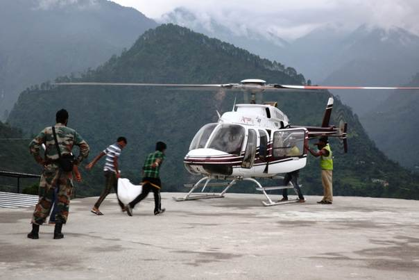 Helpers load a private helicopter with relief materials for survivors in Guptkashi town in India's Himalayan state of Uttarakhand, a month after floods and landslides hit the region. July 17, 2013. Photo Nita Bhalla/Thomson Reuters Foundation.