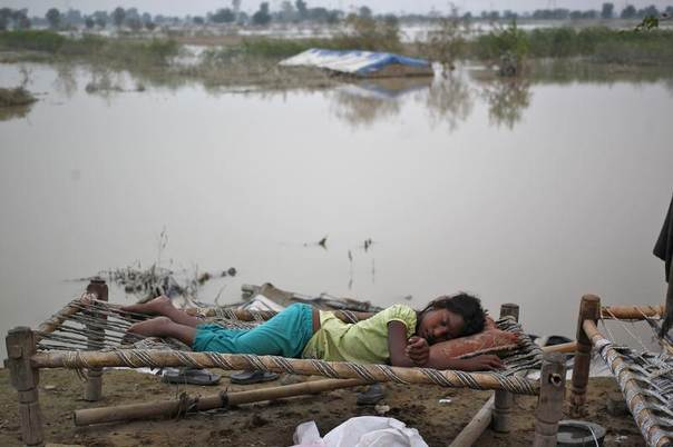 A displaced girl sleeps outside her makeshift tent at a camp by the roadside after waters rose in the river Yamuna due to heavy rains in New Delhi, India, June 21, 2013. REUTERS/Anindito Mukherjee