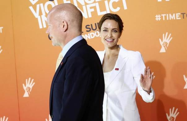 Actress and special envoy of the UN High Commissioner for Refugees (UNHCR), Angelina Jolie, waves as she arrives with British Foreign Secretary William Hague, at a global summit to end sexual violence in conflict, in London, June 10, 2014.  REUTERS/Andrew Winning