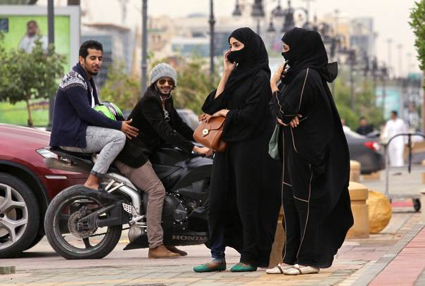 A woman speaks on the phone as men ride a motorcycle on a cloudy day in Riyadh, on Nov. 17, 2013. REUTERS/Faisal Al Nasser