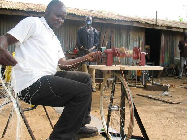 Alex Odundo demonstrates how a hand operated machine makes twine from sisal fiber. THOMSON REUTERS FOUNDATION/Pius Sawa