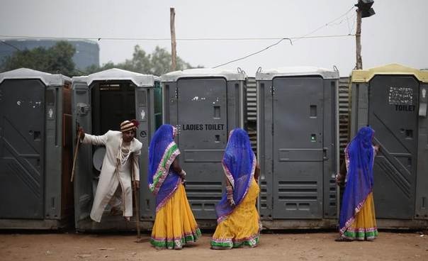 A groom leaves a toilet as brides stand ready for a mass wedding ceremony for 92 couples at Ramlila ground in New Delhi. Picture June 15, 2014, REUTERS/Adnan Abidi