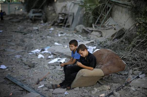 Palestinian boys sit on a sofa outside their house, which witnesses said was damaged in an Israeli air strike, in Gaza City, August 2, 2014. REUTERS/Suhaib Salem