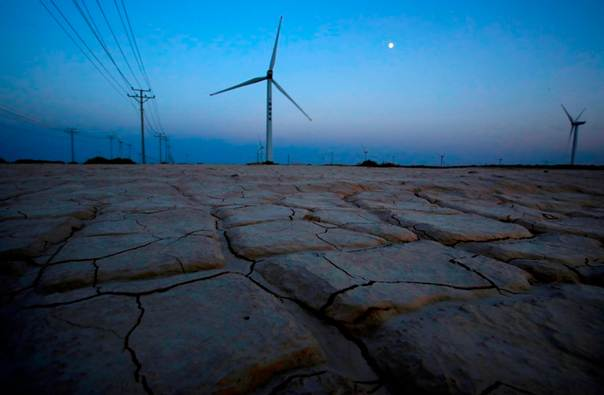 Cracked earth marks a dried-up area near a wind turbine used to generate electricity at a wind farm in Guazhou, 950km (590 miles) northwest of Lanzhou, Gansu Province, China, Sept. 15, 2013. REUTERS/Carlos Barria