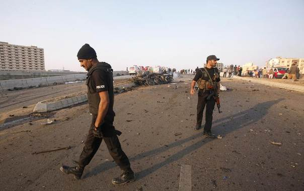 Policemen patrol the site of a vehicle bomb attack in Karachi, Pakistan, January 9, 2014. REUTERS/Athar Hussain
