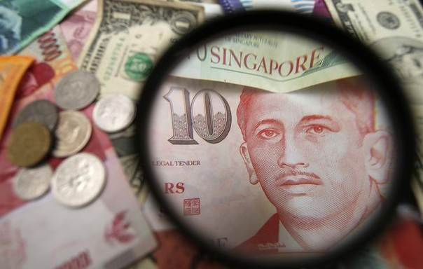 Singapore currency notes are seen through a magnifying glass among other currencies in this photo illustration taken in Singapore April 12, 2013 REUTERS/Edgar Su
