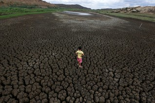 Natan Cabral, 5, stands on the dried up Boqueirao reservoir in Brazil
