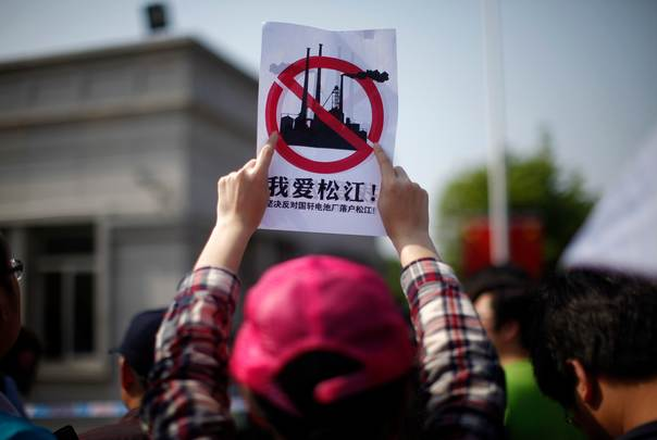 A woman holds a sign as she participates in a protest against a battery factory in front of the local government building of Songjiang district, on the outskirts of Shanghai, China, on May 1, 2013. REUTERS/Carlos Barria