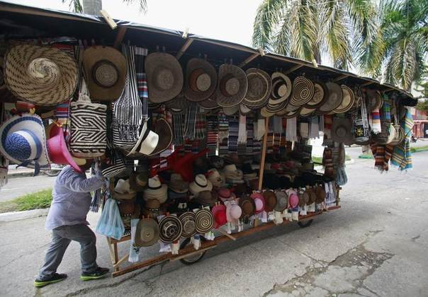 A seller pushes his home made cart with traditional hats during the 12th La Joropera festival in Acacias near Villavicencio, COlombia, October 14, 2012. AREUTERS/John Vizcaino