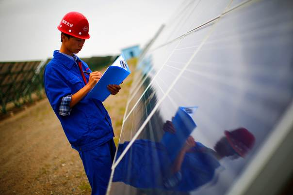 A worker inspects solar panels in Dunhuang, China.  The country is pumping investment into wind power, a more cost-competitive option than solar energy which is partly able to compete with coal and gas. China is the world's biggest producer of CO2 emissions, but is also the world's leading generator of renewable electricity. Sept. 15, 2013 REUTERS/Carlos Barria