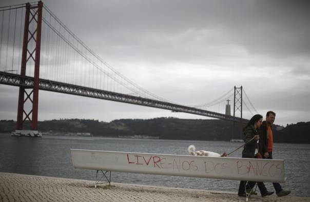 A couple walks near a bench with graffiti in Lisbon March 25, 2014. The graffiti reads,