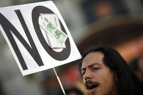 In this 2013 file photo, a demonstrator holds a sign with a fake bill and an envelope during a protest in Madrid REUTERS/Susana Vera