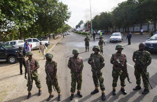 Nigerian army soldiers stand guard as they cordon off a road leading to the scene of a blast at a business district in Abuja, June 25, 2014. REUTERS/Afolabi Sotunde