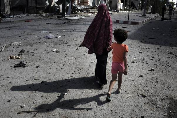 Palestinians walk through Beit Hanoun town, which witnesses said was heavily hit by Israeli shelling and air strikes during an Israeli offensive, in the northern Gaza Strip July 26, 2014. REUTERS/Finbarr O'Reilly