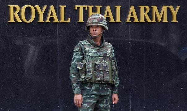 A Thai soldier stands guard outside the Royal Thai Army Headquarters as members of the Radio and Satellite Broadcasters gather in Bangkok June 18, 2014 REUTERS/Chaiwat Subprasom