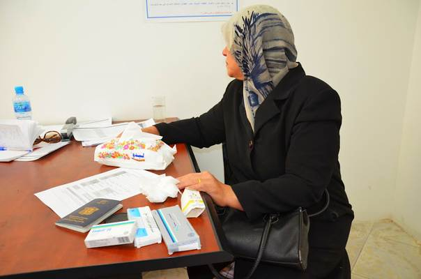 This Syrian refugee, an elderly widow living by herself in Amman, shows CARE Urban Refugee Centre staff the medication she managed to take with her when fleeing Syria. She is concerned about what will happen when her current medication runs out. Photo: Adel Sarkozi/CARE