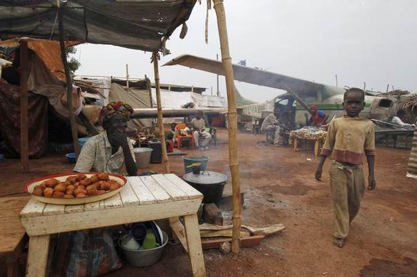 A boy displaced by inter-communal violence in the country walks past a vendor in a camp for displaced persons at Bangui M'Poko International Airport February 11, 2014. REUTERS/Luc Gnago