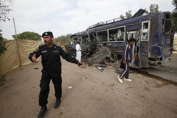 A security official prevents members of the media from approaching a damaged police bus at the site of an explosion in Karachi, Pakistan, February 13, 2014. REUTERS/Athar Hussain
