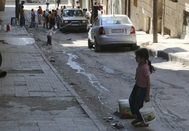 A girl drags containers of water in Bustan al-Basha district in Aleppo May 13, 2014. REUTERS/Mahmoud Hebbo