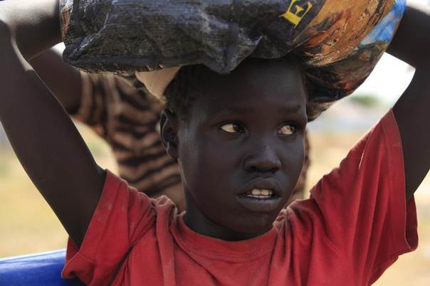 A girl, displaced by fighting, carries her belongings as she returns to her village outside Bor, South Sudan, to find her relatives,  January 25, 2014. REUTERS/Andreea Campeanu
