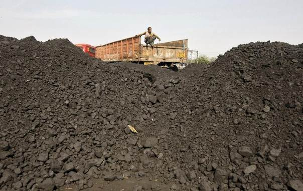 A worker sits on a truck as he waits for coal to be loaded at a railway coal yard on the outskirts of the western Indian city of Ahmedabad Nov. 25, 2013. REUTERS/Amit Dave