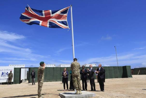 Britain's soldiers hoist their flag at their embassy as Somali President Hassan Sheikh Mohamud (3rd R), Britain's Foreign Secretary William Hague (2nd R) and other officials applaud, in Somalia's capital Mogadishu April 25, 2013. REUTERS/Feisal Omar