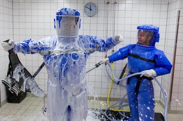 Doctors are hosed down in the disinfection chamber at the quarantine station for patients with infectious diseases at the Charite hospital in Berlin which is equipped to treat patients with Ebola. Photo taken August 11, 2014. REUTERS/Thomas Peter