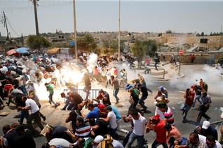 Palestinians react following tear gas that was shot by Israeli forces after Friday prayer on a street outside Jerusalem's Old city
