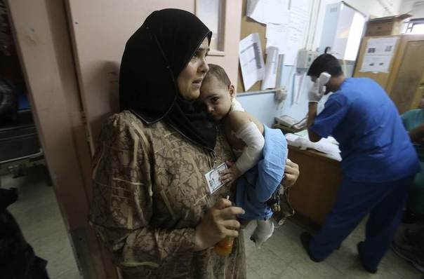 A Palestinian woman carries her son, whom medics said was wounded in an Israeli air strike, at a hospital in Khan Younis in the southern Gaza Strip July 30, 2014. REUTERS/Ibraheem Abu Mustafa