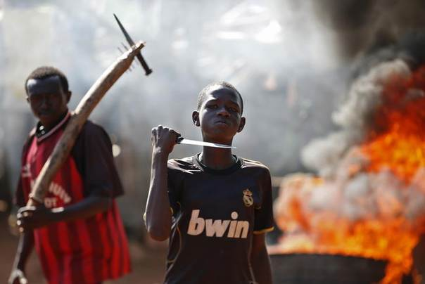 A boy gestures in front of a barricade on fire during a protest after French troops opened fire at protesters blocking a road in Bambari May 22, 2014. REUTERS/Goran Tomasevic