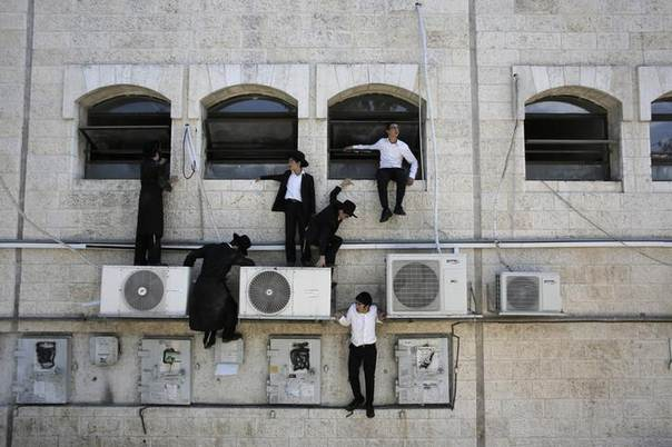 Ultra-Orthodox Jewish boys climb down a wall near the scene of a suspected attack in Jerusalem August 4, 2014. REUTERS/Ammar Awad