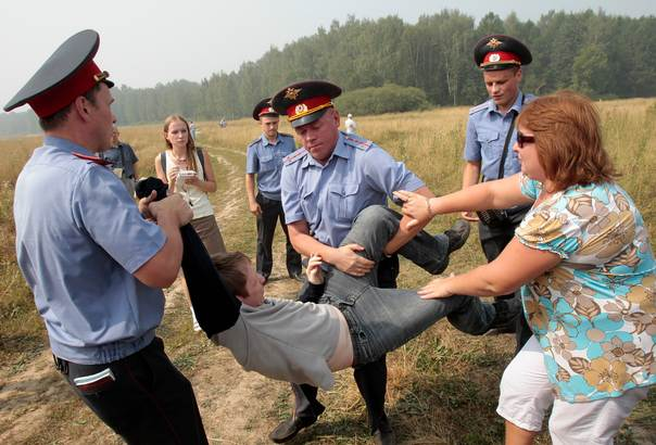Policemen detain a member of the movement for the protection of Khimki forest for attempting to reach the site of its deforestation, outside Moscow on August 2, 2010. REUTERS/Alexander Natruskin