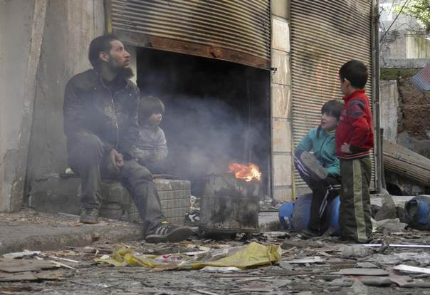 A man and children sit around a fire in the besieged area of Homs, January 30, 2014. REUTERS/Thaer Al Khalidiya