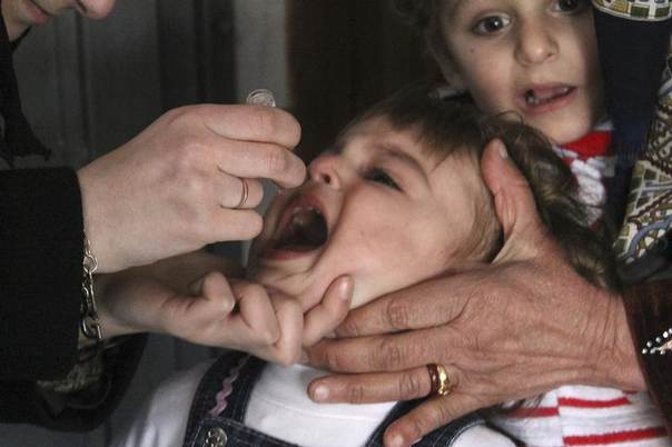 An activist health worker administers a polio vaccination to a child in Aleppo, Syria, January 5, 2014. REUTERS/Hosam Katan
