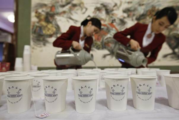 Attendants pour water into paper cups inside the Great Hall of the People at Tiananmen Square during the opening session of the National People's Congress in Beijing, March 5, 2014. REUTERS/Kim Kyung-Hoon