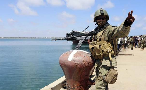 A Somali military officer guards the dock at the southern port city of Kismayu, November 1, 2013. REUTERS/Feisal Omar