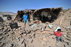 A man and a child stand at debris of a building after an earthquake in Acari, Peru
